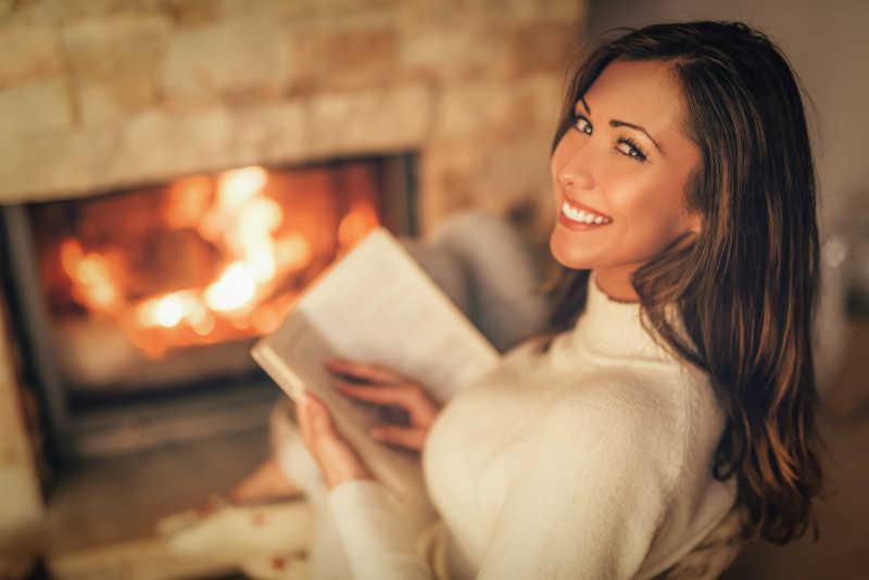 美丽的年轻女人在读书壁炉边享受