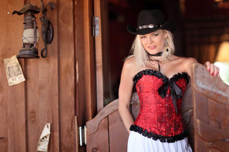 性感的女人穿着红色紧身胸衣站在老酒吧门口
