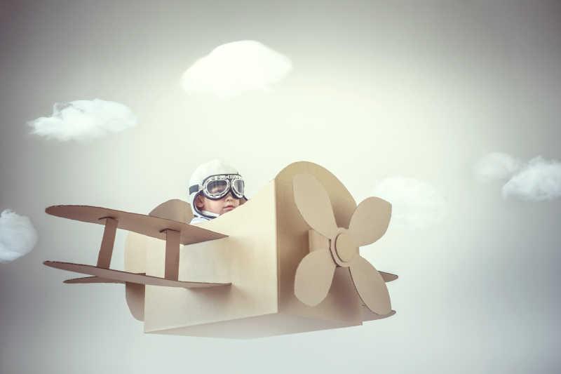 坐在纸飞机里的飞行员小男孩