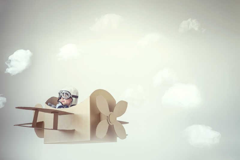 在纸飞机模型上飞行的小男孩