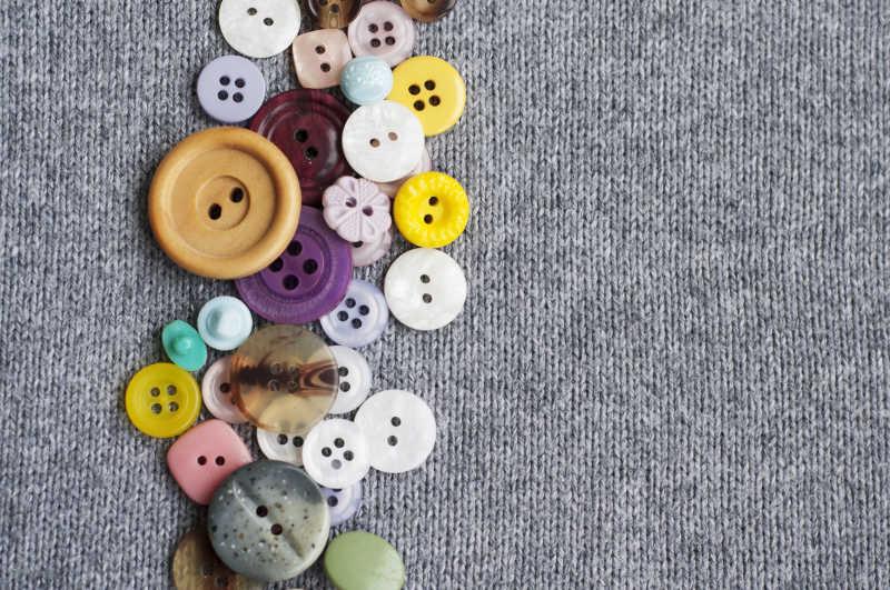 灰色针织衣服上的彩色纽扣