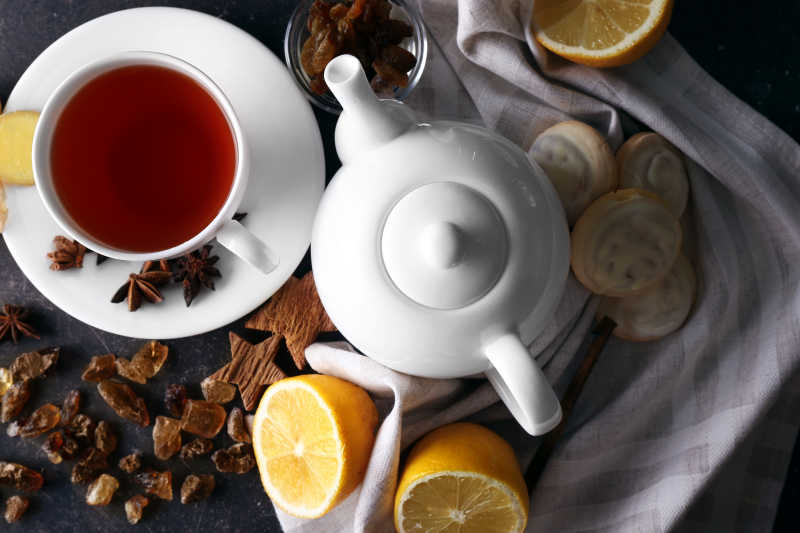 倒满水果茶的杯子和茶壶