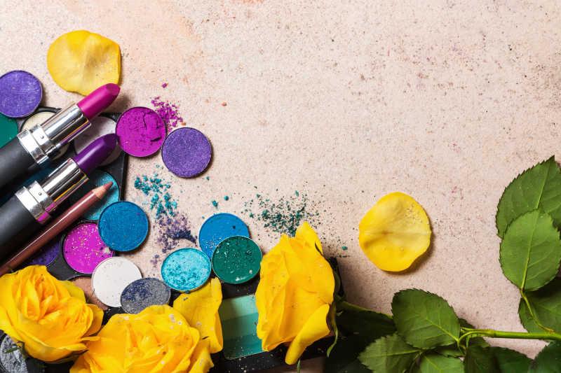 桌子上的黄色花朵彩妆口红和散落的眼影