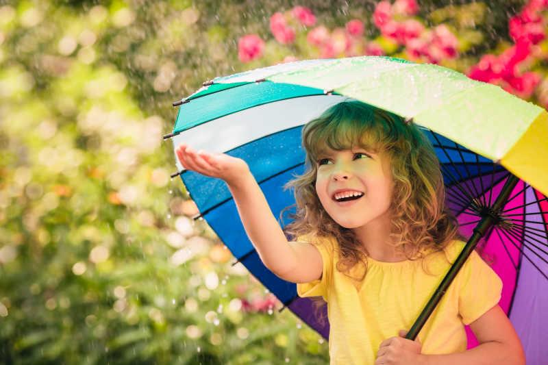 撑着伞的孩子用手触摸雨水