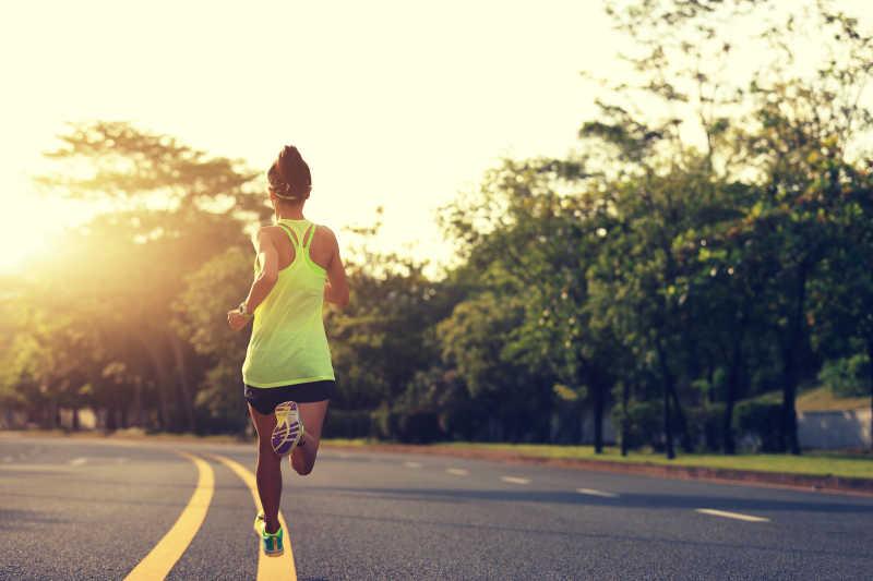 年轻女子健身运动员跑在路上