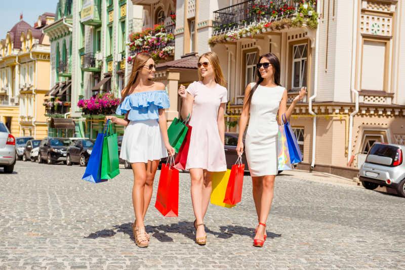 街道上提着购物袋的三个年轻美女