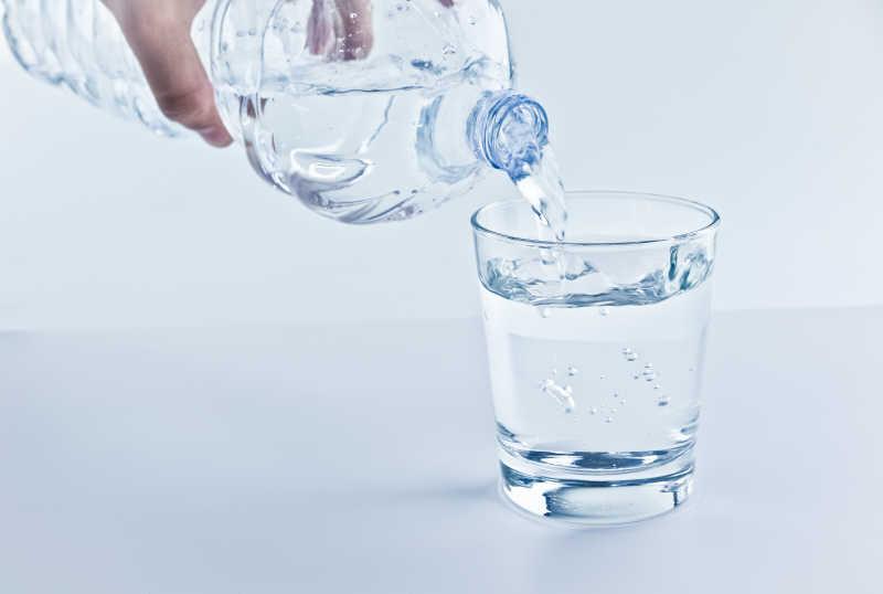 用矿泉水往杯子里倒水