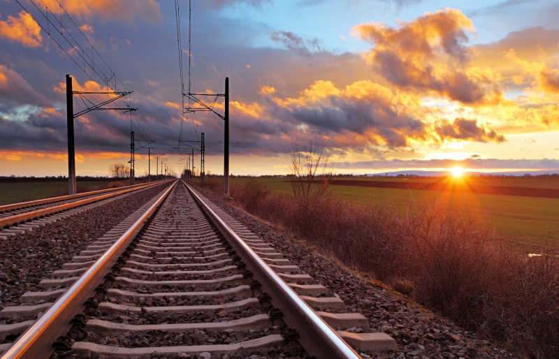 橙色夕阳下的火车铁轨