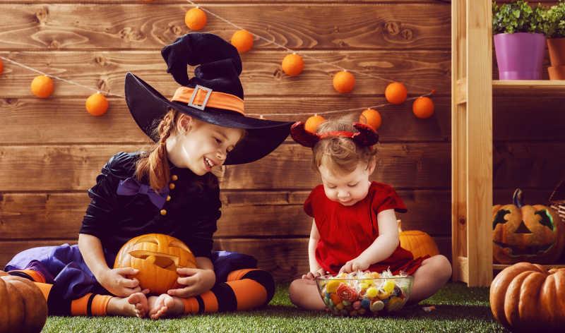 万圣节装饰背景下开心玩耍的两个小女孩