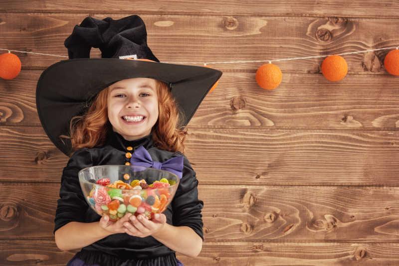 万圣节装饰背景下拿着糖果的快乐小女孩