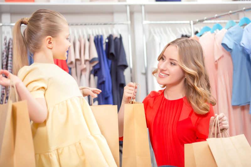 快乐的母亲带着她的女儿和大量新的购买物品