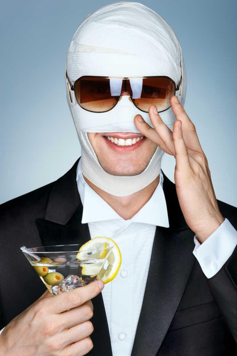 整容后脸上绑绷带的男子面带微笑手拿马蒂尼鸡尾酒杯