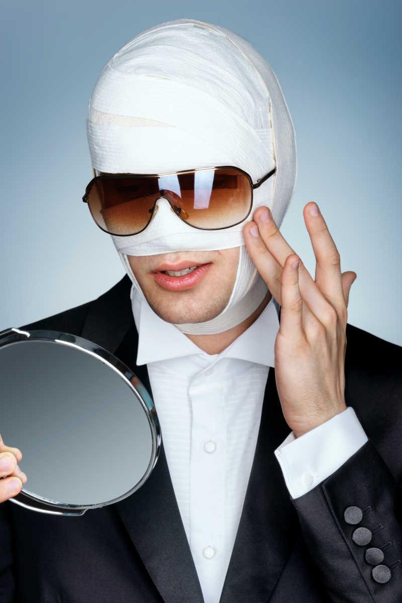 一位脸上绑绷带的男子在照镜子