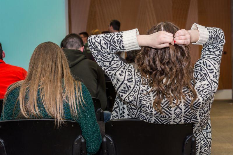 听演讲时抓着头发的女人背影