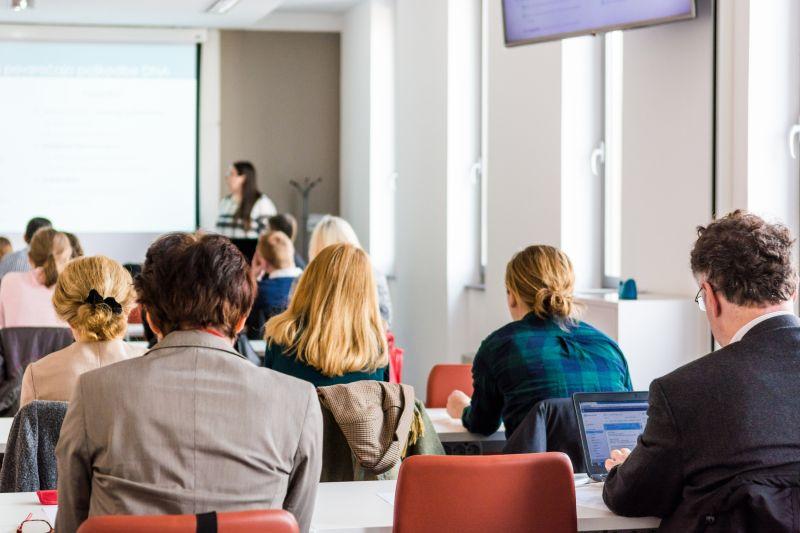 会议室里讲解内容的女商人和听讲的一群年轻人