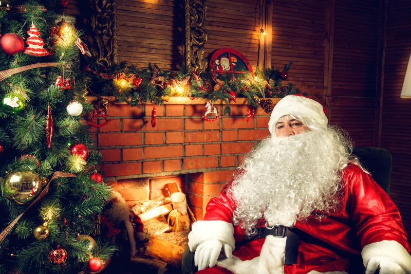 圣诞老人坐在圣诞树前