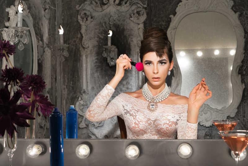 化妆镜前为自己画腮红的复古美女