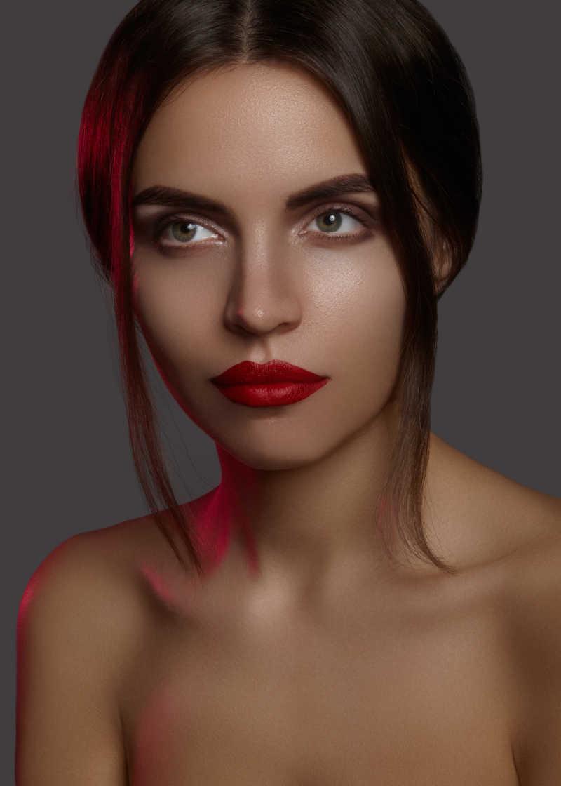 灰色背景上画着红唇的半裸时尚化妆模特