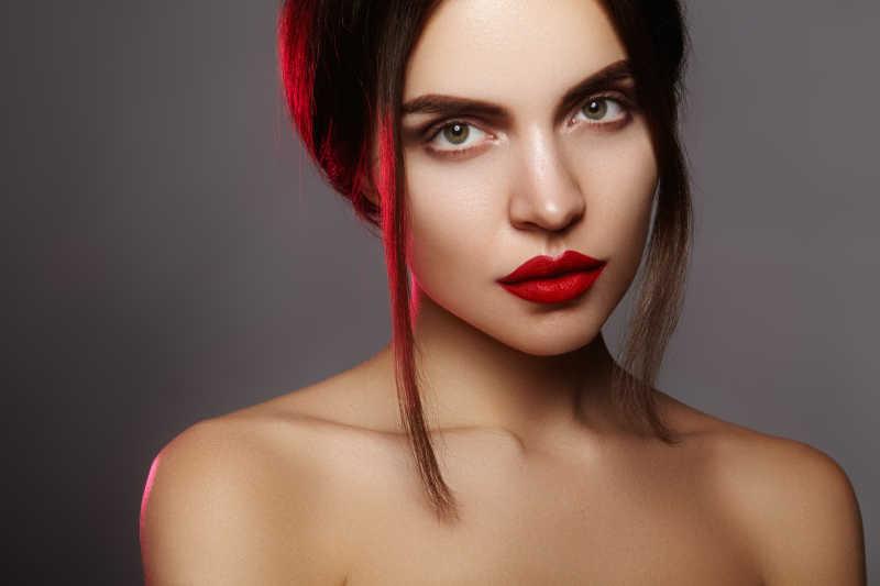 灰色背景上的有着性感红唇的半裸时尚化妆模特