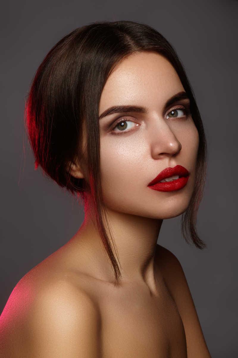 灰色背景上有着性感红唇的半裸时尚化妆模特