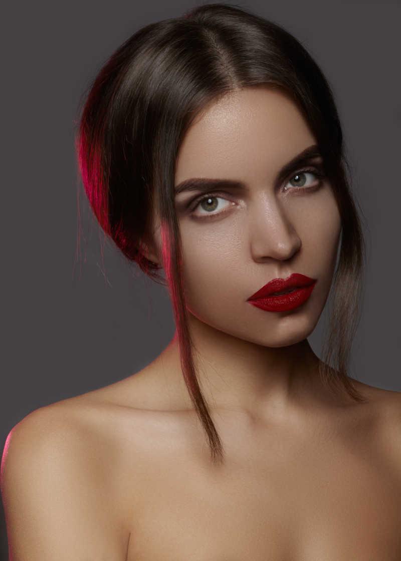 灰色背景上涂着性感红唇的半裸时尚化妆模特