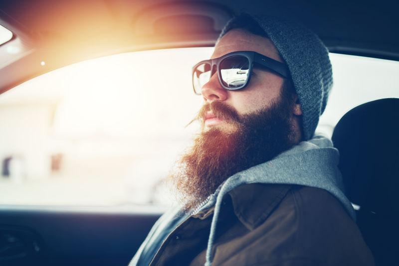 开车戴着太阳镜的胡须男子