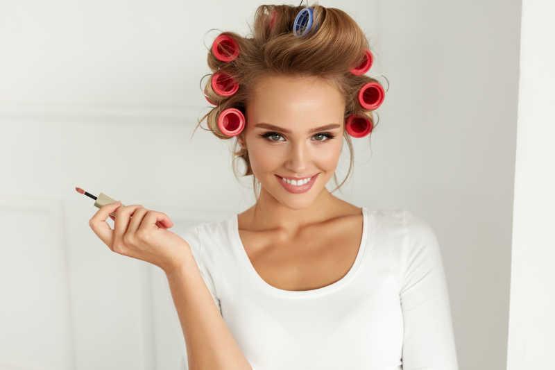 拿着口红的年轻美女在卷发