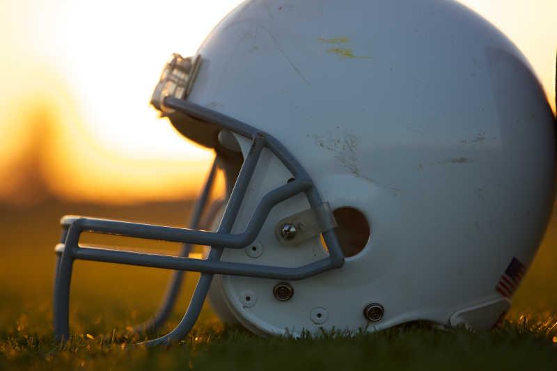 日落时放在草地上的美式橄榄球头盔
