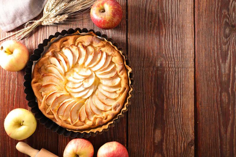 木质餐桌上的苹果派和苹果