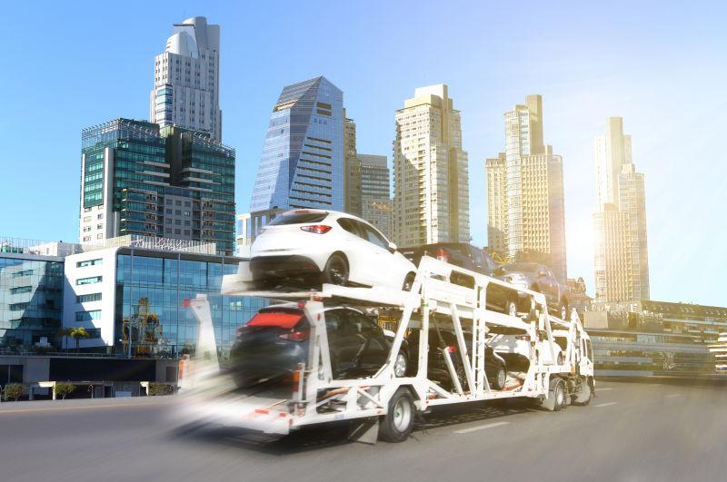 在城市的街道上行驶的运输新车的卡车