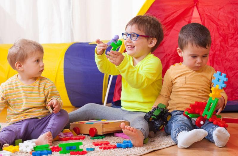 坐在地板上玩玩具孩子们