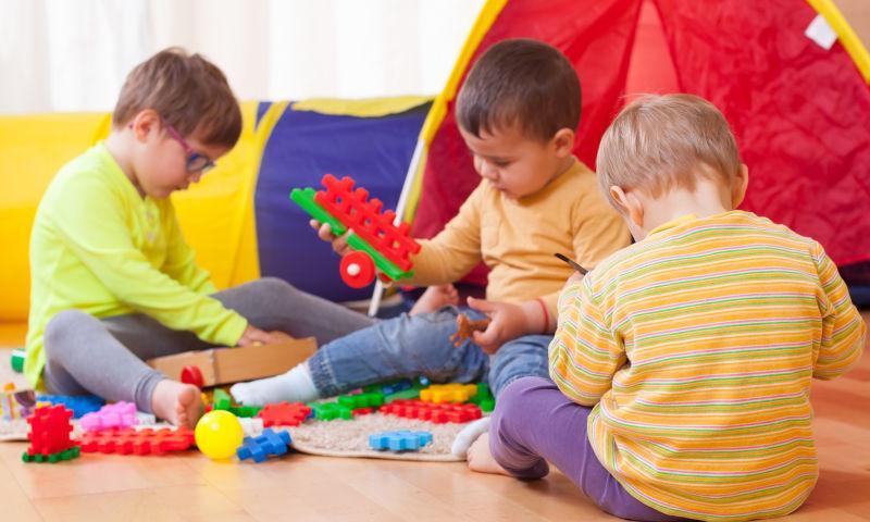 坐在地板上正在玩玩具的孩子们
