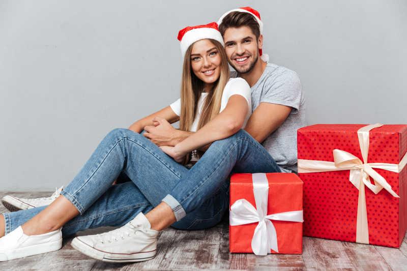 一对外国情侣边上有两个圣诞礼物盒