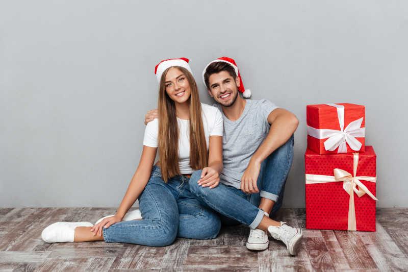 圣诞礼物边的带着圣诞帽的情侣