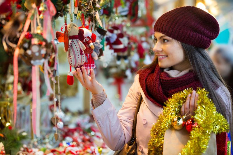 微笑的年轻黑发女人在选择圣诞装饰