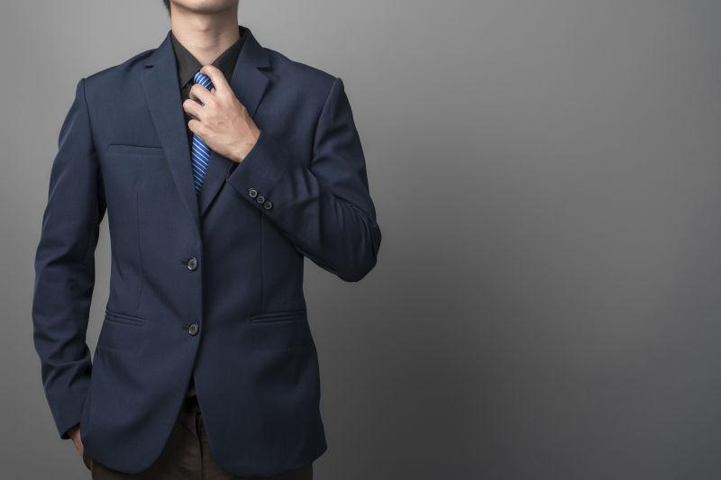 灰色背景下调整领带的商人