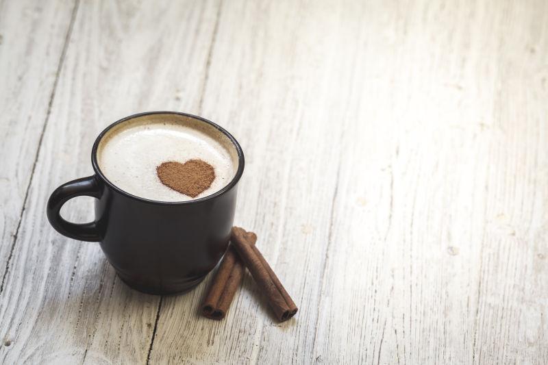 木桌上的桂皮和心形咖啡