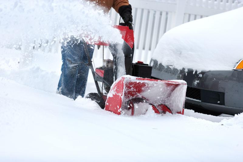 屋主用吹雪机清除车道上的积雪