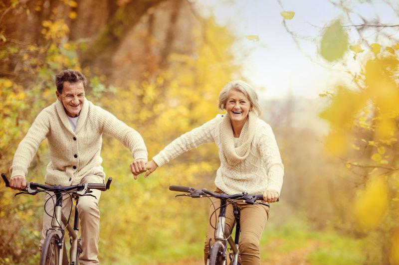 老年夫妇一起牵手骑自行车