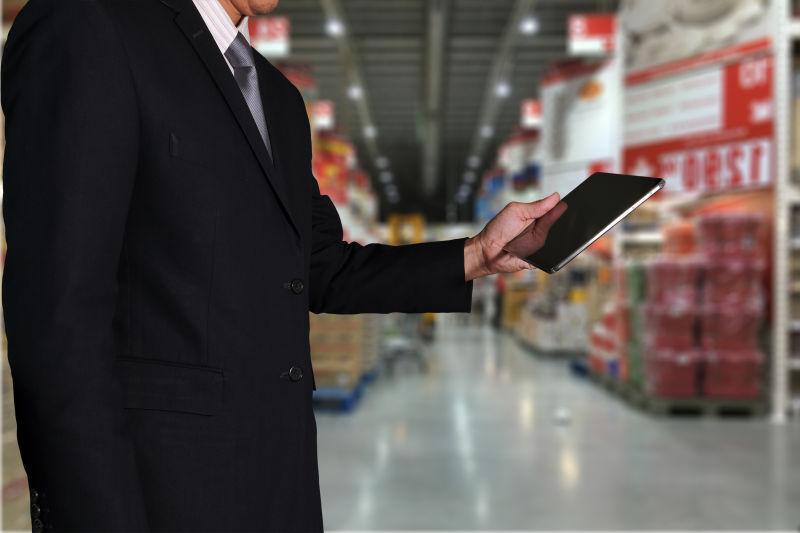 百货商场背景下使用平板的商人作为技术和商务概念的双重曝光