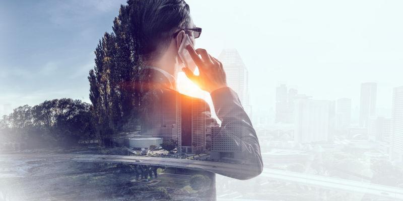 城市和打电话的商人的双重曝光