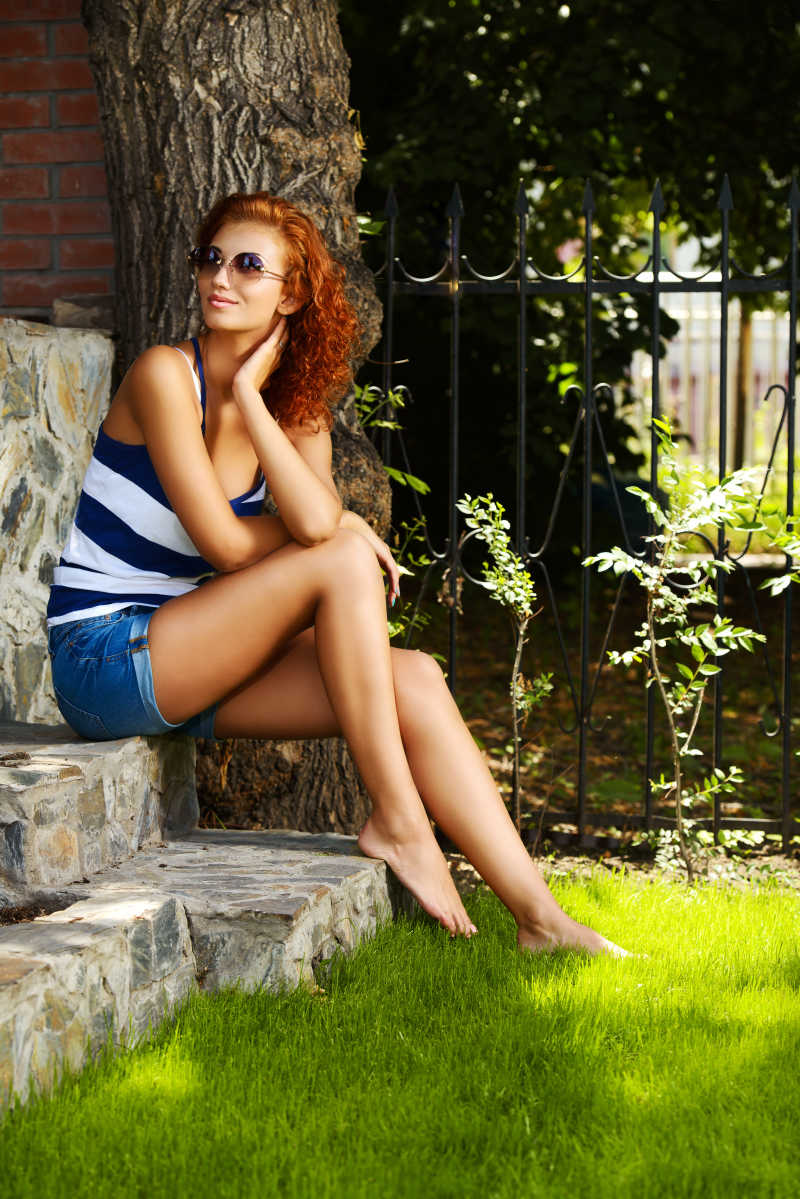 树荫下坐在台阶上的美女